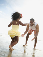 Black father bending to greet daughter on beach