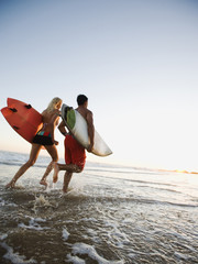 Couple running on beach carrying surfboards