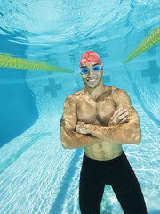 Mixed race man standing underwater in swimming pool