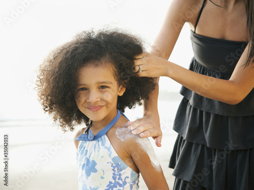 Hispanic mother rubbing sunscreen on daughter at beach