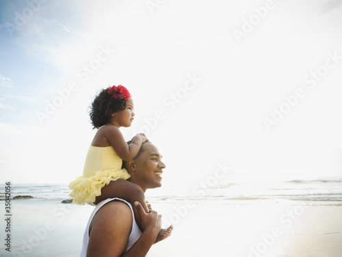 Black father carrying daughter on shoulders at beach