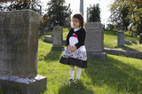 Hispanic girl with rose visiting cemetery