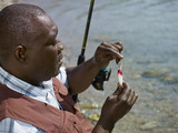 Black man putting lure on fishing pole