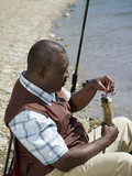 Black man removing fish from hook near stream