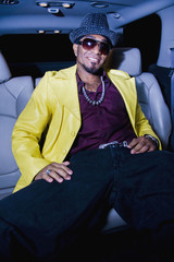 Hip African American man sitting in back seat of car