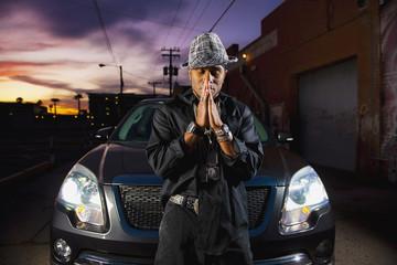 Hip African American man praying near car at night