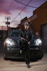 Hip African American man leaning on car hood
