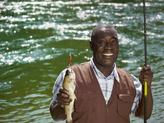 Black man holding fish and fishing rod near stream