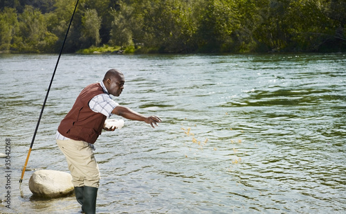 Black man throwing chum into stream