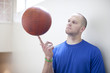 Caucasian man spinning basketball on finger