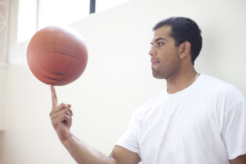 Hispanic man spinning basketball on finger