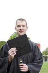 Caucasian graduate holding graduation cap
