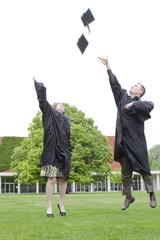 Graduates throwing graduation caps into air