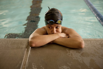 Unhappy Pacific Islander swimmer leaning at edge of pool