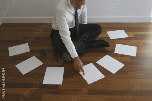 Mixed race businessman choosing paper on floor