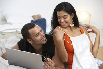 Hispanic woman showing lingerie to husband