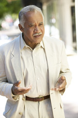 Uncertain Hispanic man standing outdoors