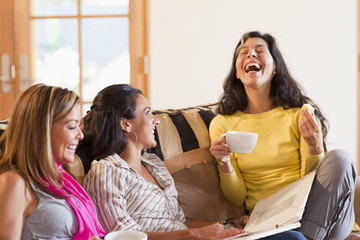 Hispanic friends laughing and drinking coffee