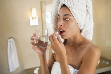 Mixed race woman taking vitamins in the morning