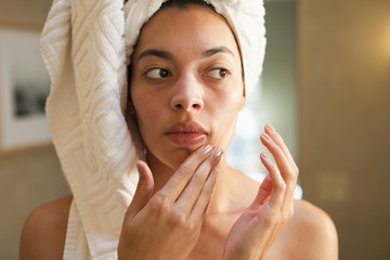 Mixed race woman rubbing face in the morning