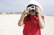 Hispanic girl using old-fashioned camera on beach