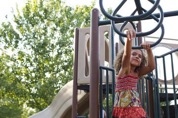 Mixed race girl playing on playground