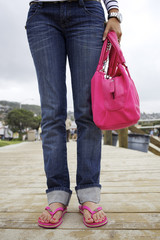Hispanic woman on boardwalk in flipflops and carrying purse