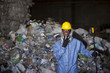 Black sanitation worker standing with garbage in recycling plant