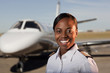 African American pilot standing near private jet