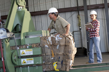 Supervisor watching sanitation worker in recycling plant