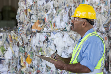Hispanic sanitation worker with clipboard in recycling plant