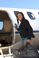 African American businesswoman boarding private jet