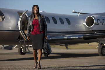 African American businesswoman standing near airplane