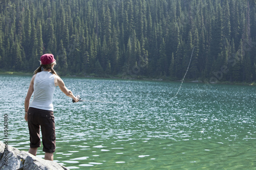Caucasian woman fishing in lake
