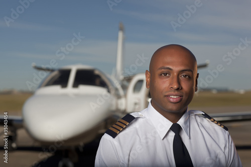 East Indian pilot standing near private jet