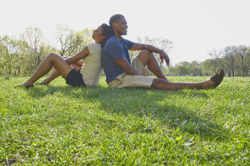 African American couple sitting in grass in park