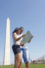 African American couple looking at map near monument