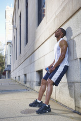 African American man leaning against wall after exercise