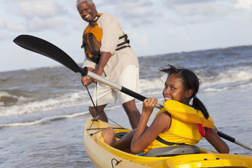 Black grandfather going kayaking with granddaughter