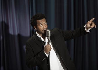 Black singer in tuxedo holding microphone