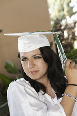 Hispanic high school graduate moving cap tassel to other side