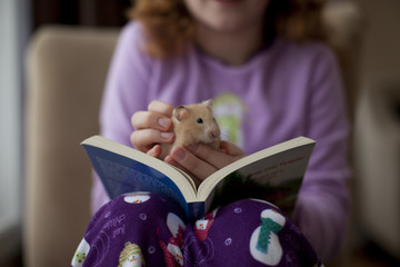 Caucasian girl sitting with book and pet hamster