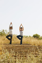 Mixed race women practicing yoga on remote staircase