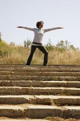 Mixed race woman practicing yoga on remote staircase
