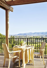 """Private dining table and chairs on a restaurant deck overlooking wine country at a luxury resort in Napa Valley, California"""