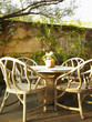 Empty chairs around a table in outdoor patio surrounded by lush foliage