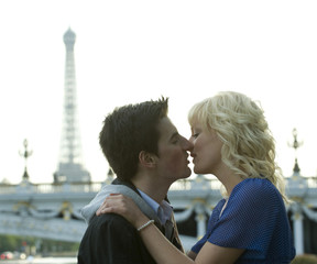 Caucasian man kissing girlfriend near Eiffel Tower