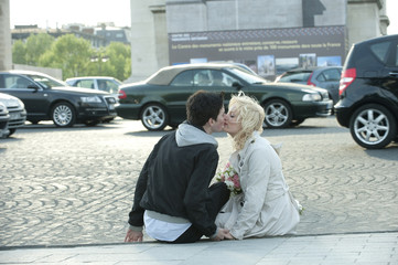 Caucasian man kissing girlfriend on busy street