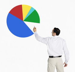 Hispanic businessman drawing pie chart on board