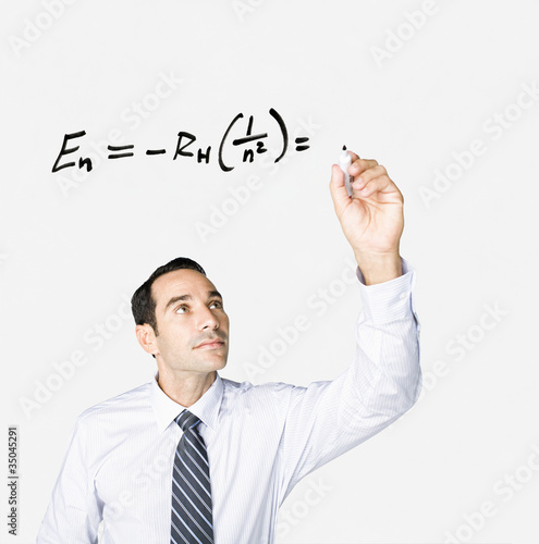 Hispanic businessman writing formula on clear board